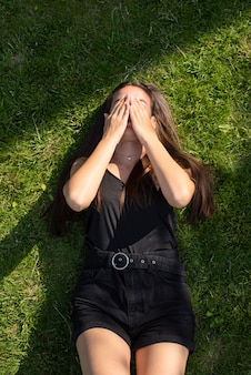 Jonge kaukasische meisjeszitting op gras en het behandelen van haar gezicht