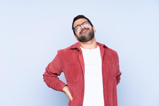 Jonge kaukasische mens die corduroy jasje over blauwe muur draagt die aan rugpijn lijdt omdat hij een inspanning heeft gedaan