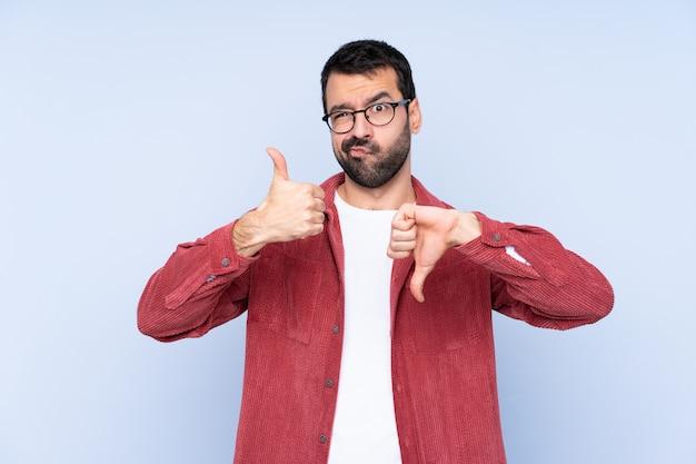 Jonge kaukasische mens die corduroy jasje over blauwe muur draagt die goed-slecht teken maakt. onbeslist tussen ja of niet