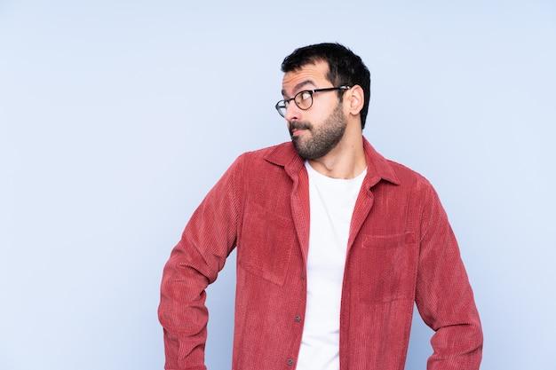 Jonge kaukasische mens die corduroy jasje over blauwe muur dragen die twijfelsgebaar maken die kant kijken