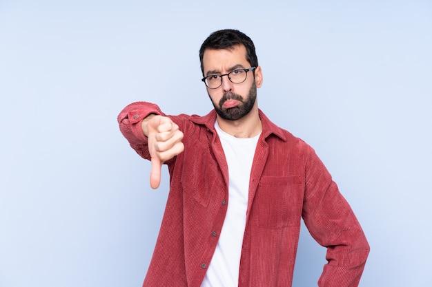 Jonge kaukasische mens die corduroy jasje over blauwe wallshowing duim met negatieve uitdrukking draagt
