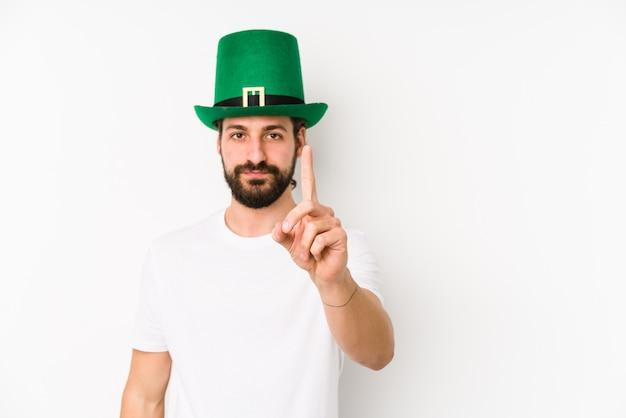 Jonge kaukasische mens die de hoed van een heilige patrick draagt die nummer één met vinger toont.