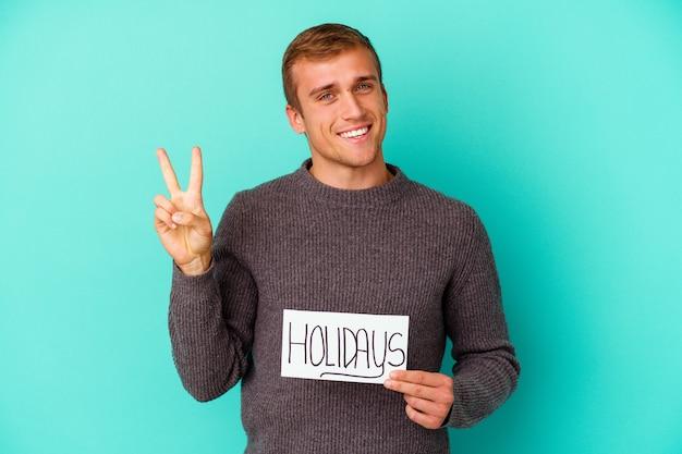 Jonge kaukasische mens die een aanplakbiljet van de vakantie houdt dat op blauw wordt geïsoleerd dat nummer twee met vingers toont.