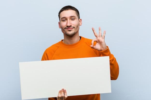 Jonge kaukasische mens die een aanplakbiljet vrolijk en zeker houdt die ok gebaar toont.
