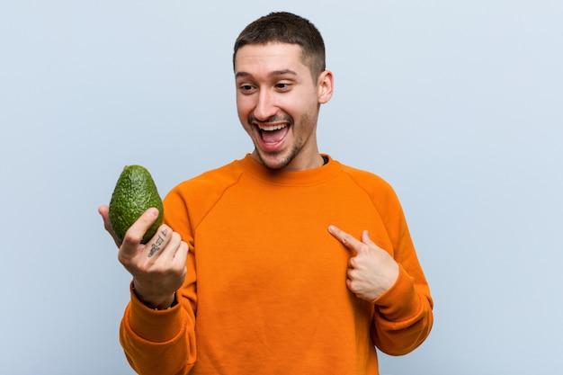 Jonge kaukasische mens die een avocado houdt verraste richtend op zich, breed glimlachend.