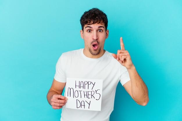 Jonge kaukasische mens die een gelukkig aanplakbiljet van de moedersdag houdt dat met een idee wordt geïsoleerd