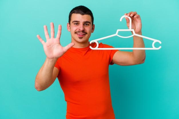 Jonge kaukasische mens die een hanger op het blauwe vrolijke glimlachen houdt die nummer vijf met vingers toont.