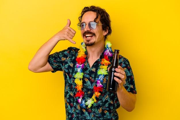 Jonge kaukasische mens die een hawaiiaanse halsband draagt die een biertje houdt dat op gele muur wordt geïsoleerd die een mobiel telefoongesprekgebaar met vingers toont.