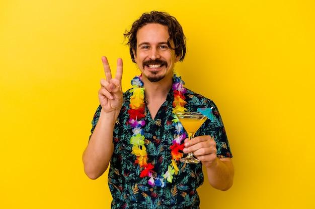 Jonge kaukasische mens die een hawaiiaanse halsband draagt die een cocktail houdt die op gele achtergrond wordt geïsoleerd die nummer twee met vingers toont.