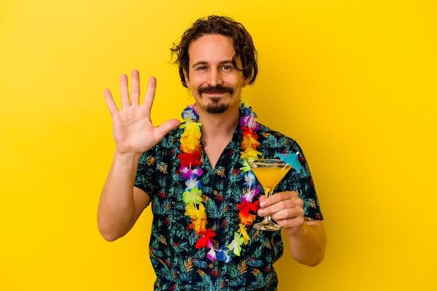 Jonge kaukasische mens die een hawaiiaanse halsband draagt die een cocktail houdt die op gele muur wordt geïsoleerd die vrolijk toont nummer vijf met vingers toont.