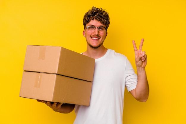Jonge kaukasische mens die een kartondoos houdt die op gele muur wordt geïsoleerd die nummer twee met vingers toont.