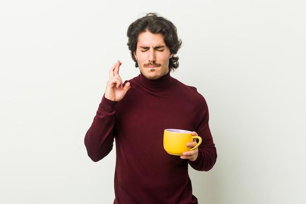 Jonge kaukasische mens die een koffiekop houdt die vingers kruist voor het hebben van geluk