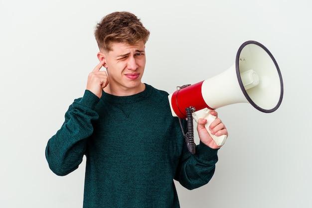 Jonge kaukasische mens die een megafoon houdt die op witte muur wordt geïsoleerd die oren met handen behandelt.