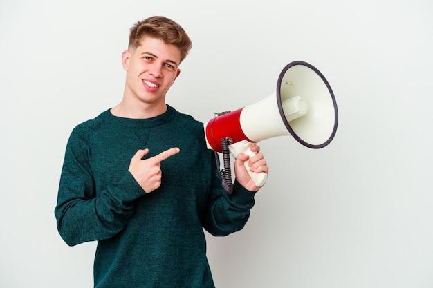 Jonge kaukasische mens die een megafoon op wit houdt die opzij glimlacht en wijst, iets op lege ruimte toont.