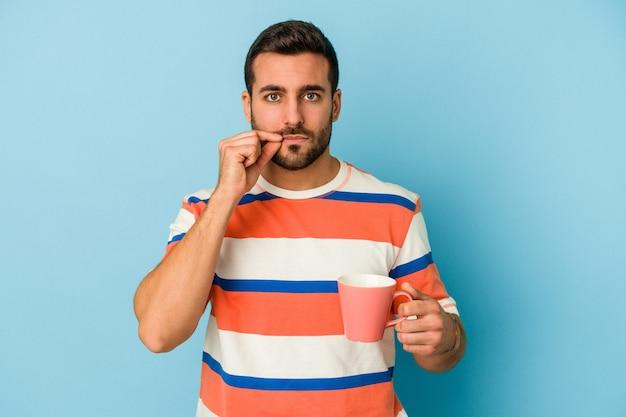 Jonge kaukasische mens die een mok houdt die op blauwe achtergrond met vingers op lippen wordt geïsoleerd die een geheim houden.