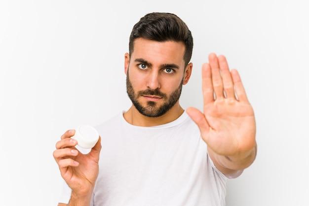Jonge kaukasische mens die een vochtinbrengende crème geïsoleerd houden zich bevindt met uitgestrekte hand die eindeteken tonen, die u verhinderen.