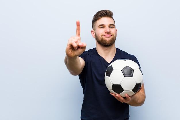 Jonge kaukasische mens die een voetbalbal houdt die nummer één met vinger toont.