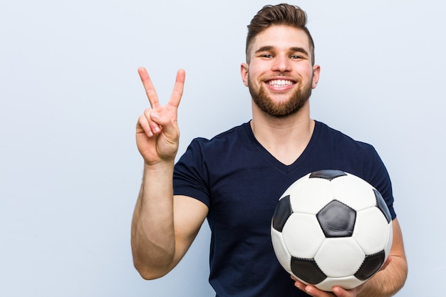 Jonge kaukasische mens die een voetbalbal houdt die nummer twee met vingers toont.