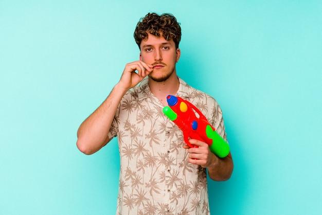 Jonge kaukasische mens die een waterpistool houdt dat op blauwe achtergrond met vingers op lippen wordt geïsoleerd die een geheim houden.