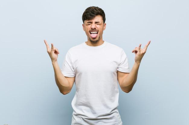 Jonge kaukasische mens die een witte t-shirt draagt die rotsgebaar met vingers toont