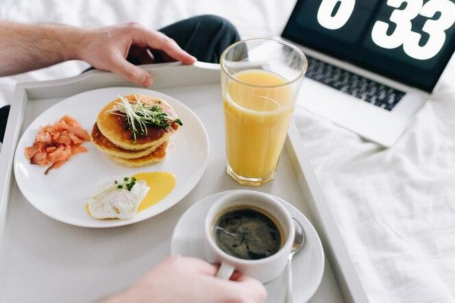 jonge kaukasische mens die gezond ontbijt in bed op dienblad eet