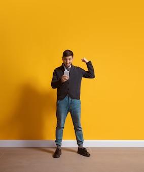 Jonge kaukasische mens die het lengteportret van het smartphone volledige lichaam gebruikt dat over gele muur wordt geïsoleerd
