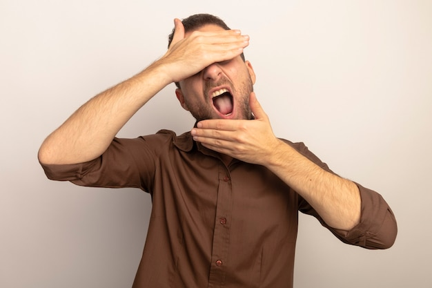Jonge kaukasische mens die ogen behandelt met hand die een andere op kin met open mond zet die op witte achtergrond wordt geïsoleerd