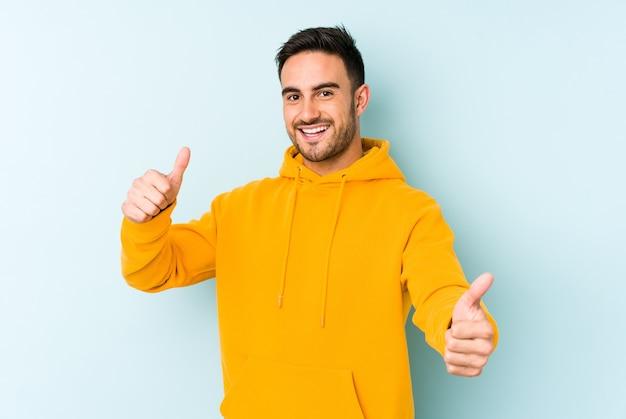 Jonge kaukasische mens die op blauwe achtergrond wordt geïsoleerd die beide duimen opheft, glimlachend en zelfverzekerd.