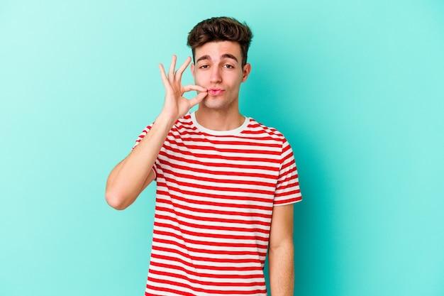 Jonge kaukasische mens die op blauwe muur met vingers op lippen wordt geïsoleerd die een geheim houden. Premium Foto