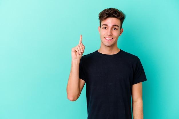 Jonge kaukasische mens die op blauwe muur wordt geïsoleerd die nummer één met vinger toont.
