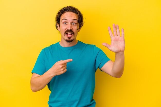 Jonge kaukasische mens die op gele achtergrond wordt geïsoleerd die vrolijk toont nummer vijf met vingers.