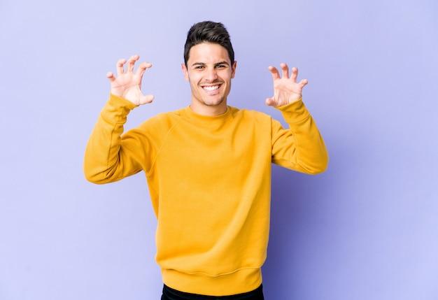 Jonge kaukasische mens die op purpere muur klauwen toont die een kat imiteren