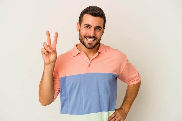 Jonge kaukasische mens die op witte muur wordt geïsoleerd die nummer twee met vingers toont.