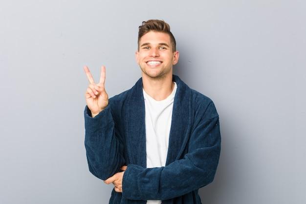 Jonge kaukasische mens die pyjama draagt die nummer twee met vingers toont.