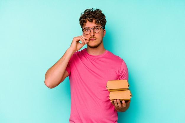 Jonge kaukasische mens die twee hamburgers houdt die op blauwe achtergrond met vingers op lippen worden geïsoleerd die een geheim houden.