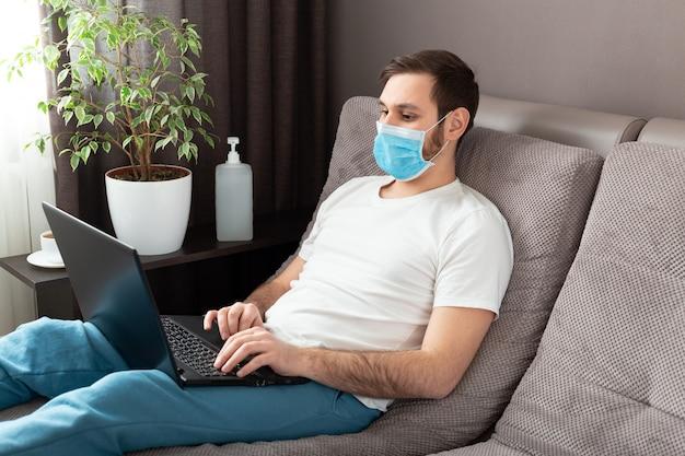 Jonge kaukasische mens die van huis werkt die beschermend masker draagt dat laptop en internet gebruikt