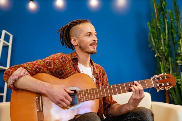 Jonge kaukasische mens met dreadlocks die op bank zitten en akoestische gitaar spelen