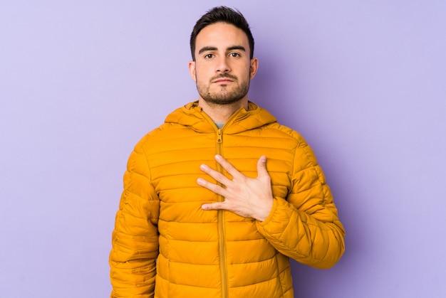Jonge kaukasische mens op purpere muur die een eed afleggen, die hand op borst zetten.