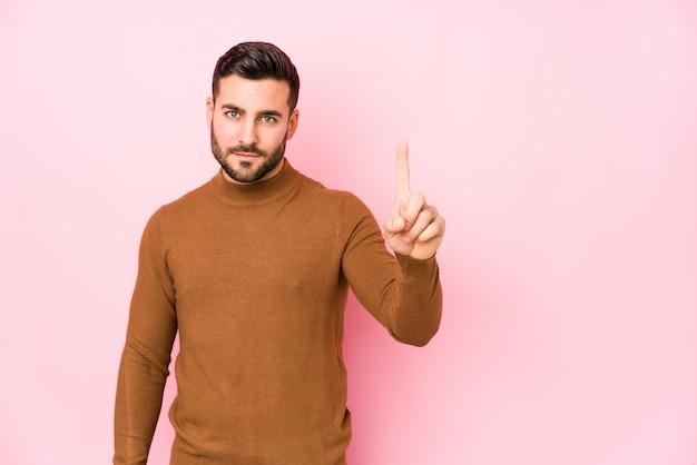 Jonge kaukasische mens tegen een roze muur die nummer één met vinger toont.