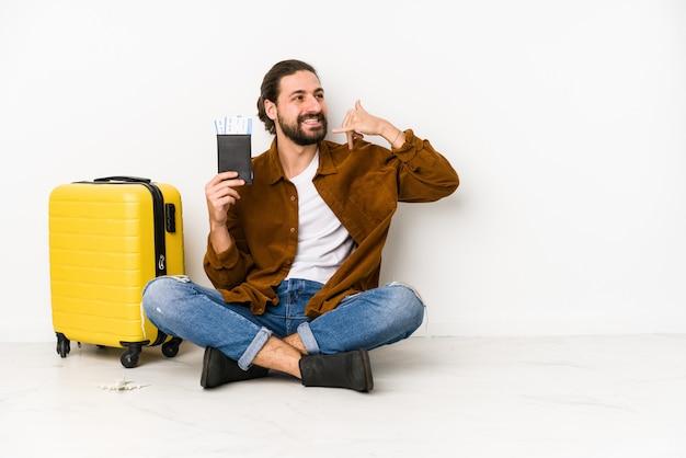 Jonge kaukasische mensenzitting die een paspoort en een koffer houden geïsoleerd tonend een mobiel telefoongesprekgebaar met vingers.