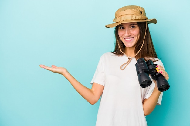 Jonge kaukasische ontdekkingsreizigervrouw die een verrekijker houdt die op blauwe achtergrond wordt geïsoleerd die een exemplaarruimte op een palm toont en een andere hand op taille houdt.