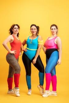 Jonge kaukasische plus grootte vrouwelijke modellen die op geel trainen