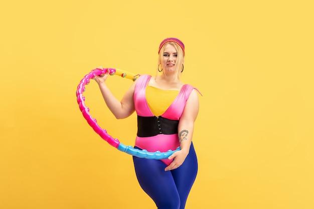 Jonge kaukasische plus size vrouwelijke model opleiding op gele achtergrond. kopieerruimte. concept van sport, gezonde levensstijl, positief lichaam, mode, stijl. stijlvolle vrouw oefenen met heldere hoepel.