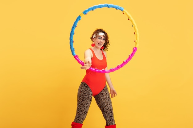 Jonge kaukasische plus size vrouwelijke model opleiding op gele achtergrond. kopieerruimte. concept van sport, gezonde levensstijl, positief lichaam, mode, stijl. stijlvolle vrouw oefenen, poseren met hoepel.