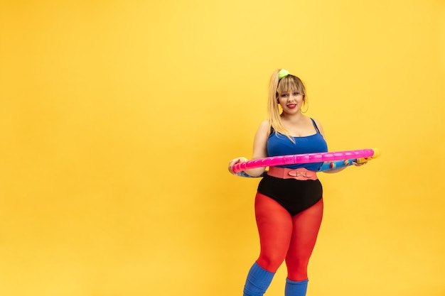 Jonge kaukasische plus size vrouwelijke model opleiding op gele achtergrond. stijlvolle vrouw in lichte kleding. kopieerruimte. concept van sport, gezonde levensstijl, lichaamspositief, mode. poseren met de hoepel.