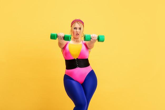 Jonge kaukasische plus size vrouwelijke model opleiding op gele muur. kopieerruimte. concept van sport, gezonde levensstijl, positief lichaam, mode, stijl. stijlvolle vrouw oefenen met groene gewichten. Premium Foto