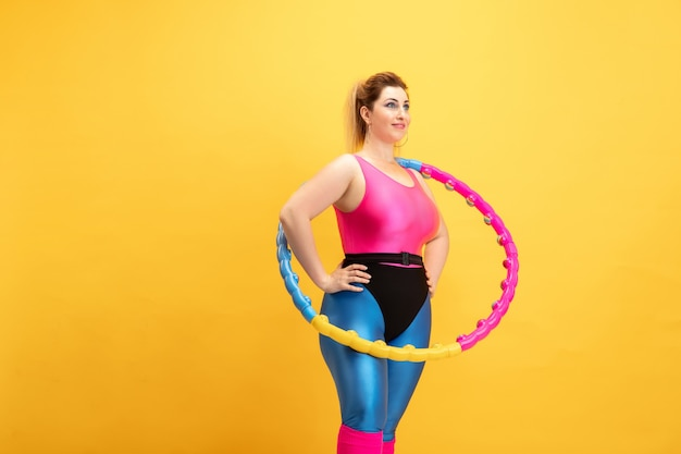 Jonge kaukasische plus size vrouwelijke model opleiding op gele muur. kopieerruimte. concept van sport, gezonde levensstijl, positief lichaam, mode, stijl. stijlvolle vrouw oefenen met hoepel en glimlachen.