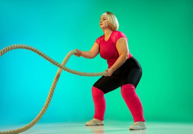 Jonge kaukasische plus size vrouwelijke model opleiding op gradiënt groene achtergrond in neonlicht. trainingsoefeningen doen met de touwen. concept van sport, gezonde levensstijl, lichaamspositief, gelijkheid.