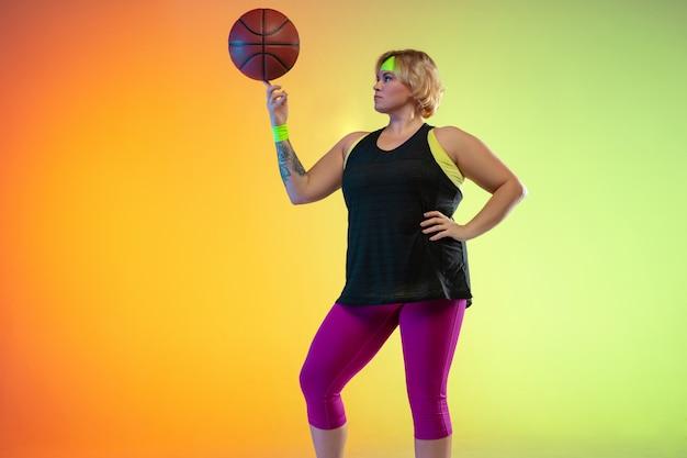 Jonge kaukasische plus size vrouwelijke model training op gradiënt oranje muur in neonlicht.