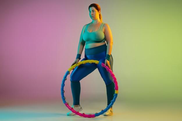 Jonge kaukasische plus size vrouwelijke model training op gradiënt paarse groene muur in neonlicht. trainingsoefeningen doen met hoepel.